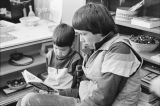 Older boy reading to a young child.