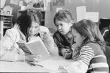 Three school girls reading.
