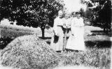 Four women with a haystack in an orchard.