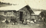 Family sitting in front of their log house at Healy Lake Village, circa 1930s.