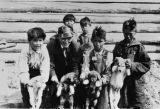 Showing off puppies at the Tanacross Mission at Old Tanacross, date unknown.
