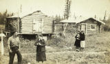 Ted Lowell, Miss Wright, Isabelle Albert, and Ada Albert in front of log houses in the village of...
