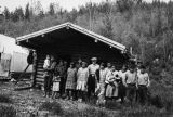 People standing in front of Abe Luke's cabin at fish camp on the Healy River, circa 1940.