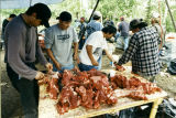 Four men cutting meat.