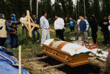 Young man with cross at graveside of Chief Peter John.
