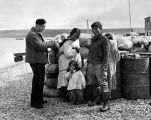 Stopover at Teller, Alaska on way to Point Barrow, 1945. Claude Tabler talks to Eskimo family.