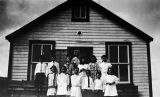 Children in front of schoolhouse.