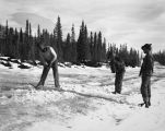 Soldiers drain water from an ice hazard on the road west of White River, February 23, 1943.