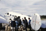 People standing outside a Twin Beech transport plane.