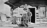 Two men and a boy in front of a log cabin