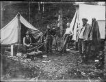 Four men outside two tents