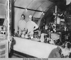 Interior view of kitchen, men working in it.