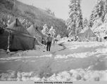 Man in front of tent in snow.