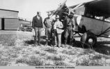 Four men standing in front of a Hamilton Fairchild on tundra tires.