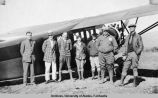 Six men and one woman standing behind the right wing of an airplane.