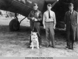 Three men and a husky standing in front of and airplane.