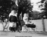 Woman with two children, one in a stroller.