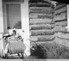 Baby in baby carriage in doorway of log house.