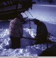 Floyd & Pete burying skis for use as anchor points to tie down the plane for the night.
