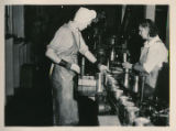Two women using can-sealing machine.