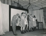 Men wearing dresses performing on stage.