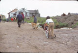 Kids using dogs to pull tricycle. Scammon Bay.