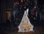Gingerbread house in front of Christmas tree.