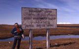 Ruth Schmidt standing beside Shishmaref Airport Sign.