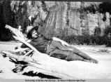 Man reclining on log with pipe, ca. 1890-1910.