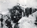 Men alongside a railroad snowplow locomotive.
