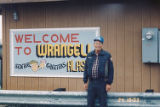 Al Beyer in front of the Welcome to Wrangell sign.