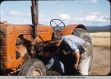 Working on tractor at Charles A. Creamer Dairy, Fairbanks.