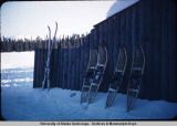 Snowshoes and skis leaning against cabin wall.