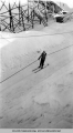 Woman on skis riding tow rope next to ski jump, ca. 1946.