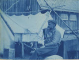 A man seated in front of a tent, 1898.