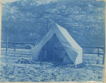 An open tent near a wooden fence in Dyea, 1898.