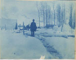 Man standing in snow in front of tent camp.