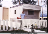 Man in front of mobile home.