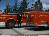 William McNutt standing between fire trucks.