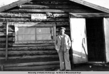 Glenn standing outside a log building in Galena, 1944-1945.