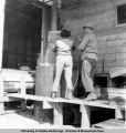 Robert Mounteer and Evelyn Haltinen removing cooking basket from vat, Aug. 1952.