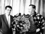 Two men with flower arrangement.