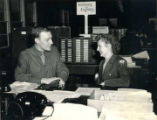 John Macomber and a woman in a military uniform sitting at a desk in a military facility.