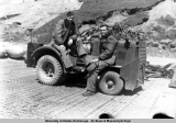 Two men on vehicle used for towing aircraft, Adak 1945.