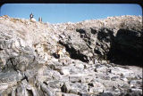 Man standing above rock pile on Baffin Island.