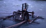 Man standing on a fish wheel.