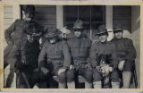 Group portrait of six soldiers and a dog.