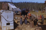 Harold Pomeroy and another man examining tools at Bear Cove.