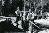 Man and woman sitting on cut lumber at Bear Cove.