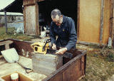 Harold Pomeroy working in his chainsaw at Bear Cove.